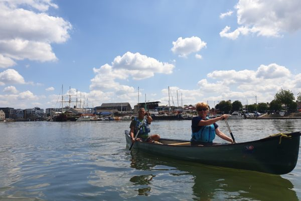 Two adults canoeing on Bristol harbour
