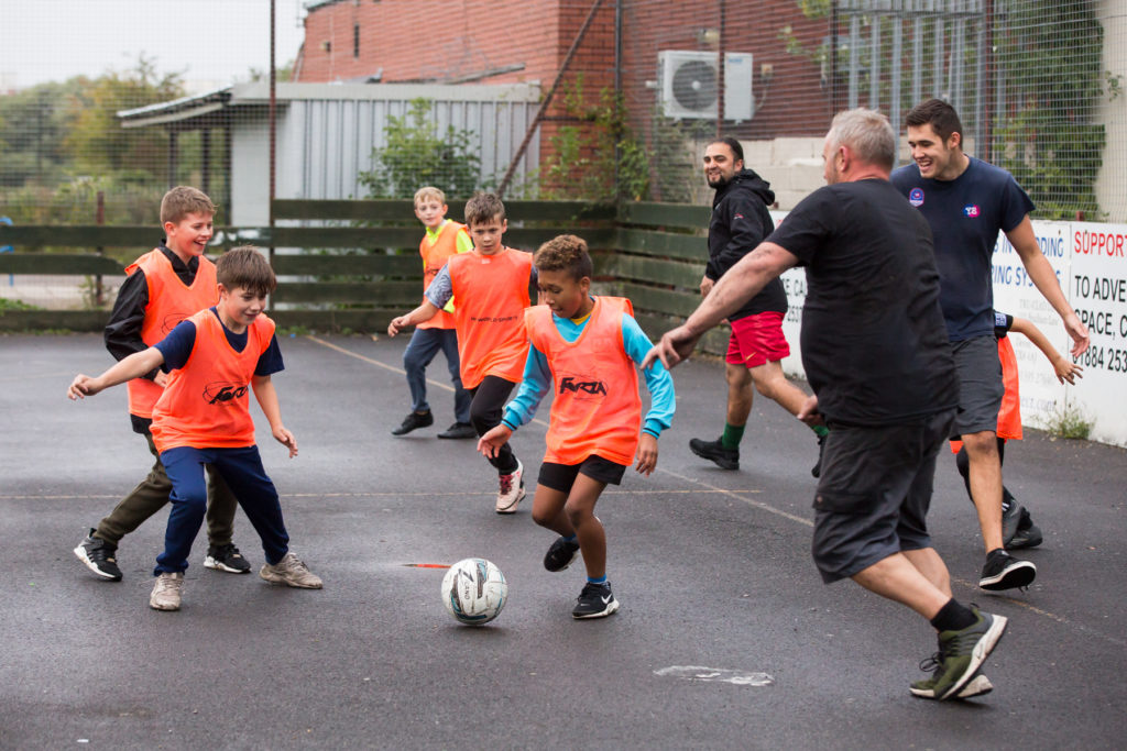 Young people playing football at club